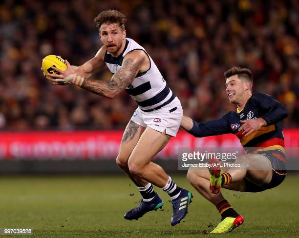 Zach Tuohy of the Cats is tackled by Bryce Gibbs of the Crows during the 2018 AFL round 17 match between the Adelaide Crows and the Geelong Cats at...