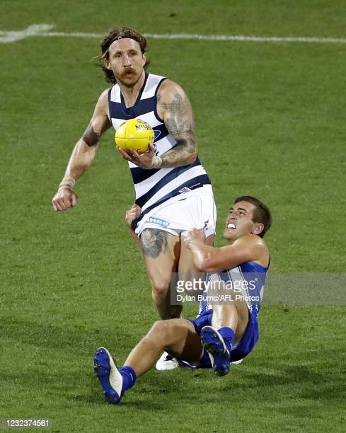 Zach Tuohy of the Cats is tackled by Will Phillips of the Kangaroos during the 2021 AFL Round 05 match between the Geelong Cats and the North...