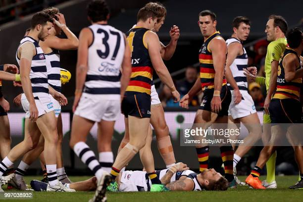 Zach Tuohy of the Cats lies on the ground after a hit by Taylor Walker of the Crows during the 2018 AFL round 17 match between the Adelaide Crows and...
