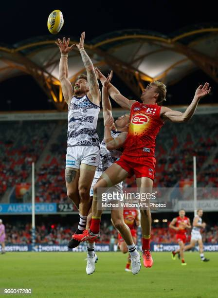 Zach Tuohy of the Cats marks the ball ahead of Tom Lynch of the Suns during the 2018 AFL round 11 match between the Gold Coast Suns and the Geelong...