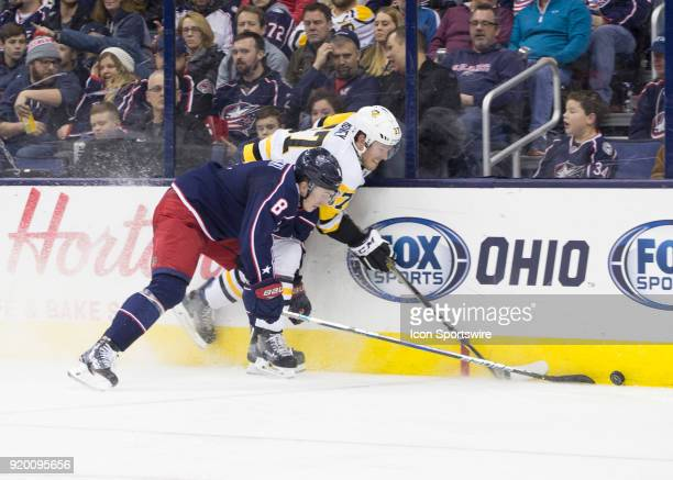 Zach Werenski of the Columbus Blue Jackets and Carter Rowney of the Pittsburgh Penguins battle for the puck along the boards during second period of...