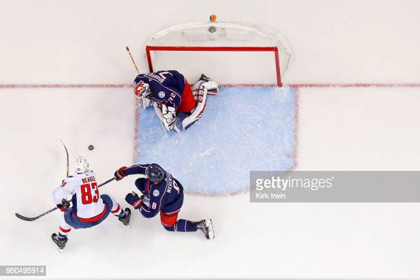 Zach Werenski of the Columbus Blue Jackets attempts to keep Jay Beagle of the Washington Capitals from getting a shot off on Sergei Bobrovsky of the...