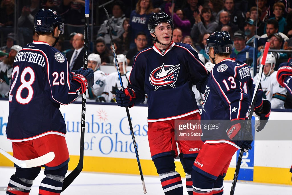 Zach Werenski #8 of the Columbus Blue Jackets celebrate his first career NHL goal with teammates Oliver Bjorkstrand #28 and Cam Atkinson #13 of the Columbus Blue Jackets during the third period of a game against the San Jose Sharks on October 15, 2016 at Nationwide Arena in Columbus, Ohio. San Jose defeated Columbus 3-2.