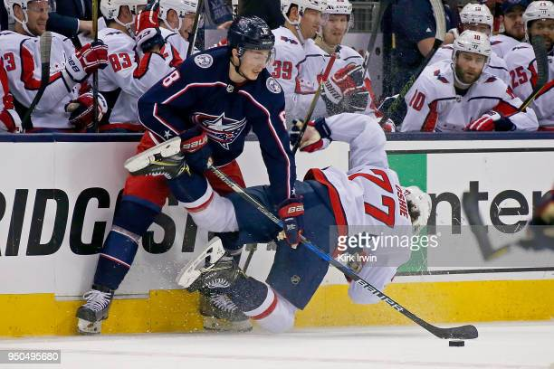 Zach Werenski of the Columbus Blue Jackets knocks over TJ Oshie of the Washington Capitals while battling for control of the puck in Game Four of the...