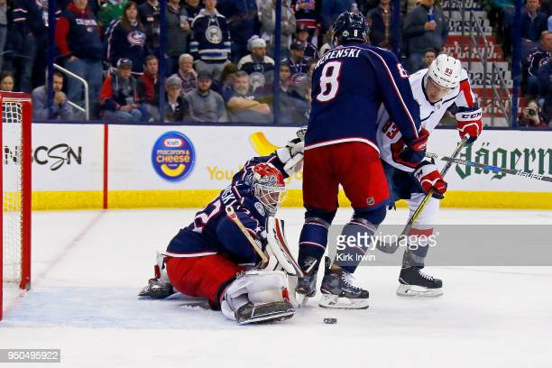 Zach Werenski of the Columbus Blue Jackets plays defense as Sergei Bobrovsky of the Columbus Blue Jackets stops a shot from Jay Beagle of the...