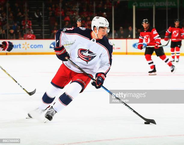 Zach Werenski of the Columbus Blue Jackets plays the puck during the game against the New Jersey Devils at Prudential Center on December 8 2017 in...