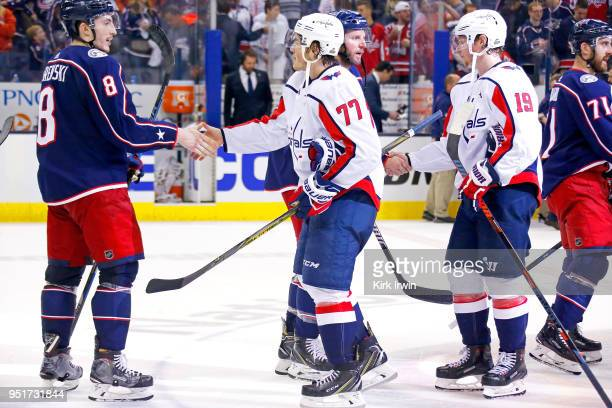 Zach Werenski of the Columbus Blue Jackets shakes hands with TJ Oshie of the Washington Capitals after the end of Game Six of the Eastern Conference...