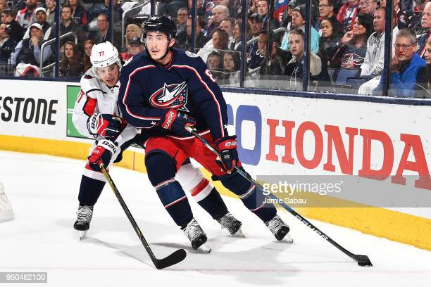 Zach Werenski of the Columbus Blue Jackets shields the puck from TJ Oshie of the Washington Capitals during the first period in Game Six of the...