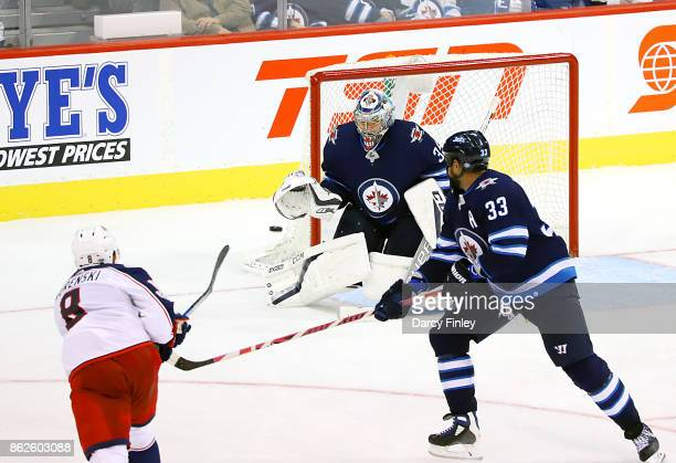 Zach Werenski of the Columbus Blue Jackets shoots the puck on goal as goaltender Steve Mason of the Winnipeg Jets defends the net during third period...
