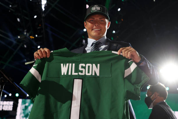 zach-wilson-holds-a-jersey-onstage-after