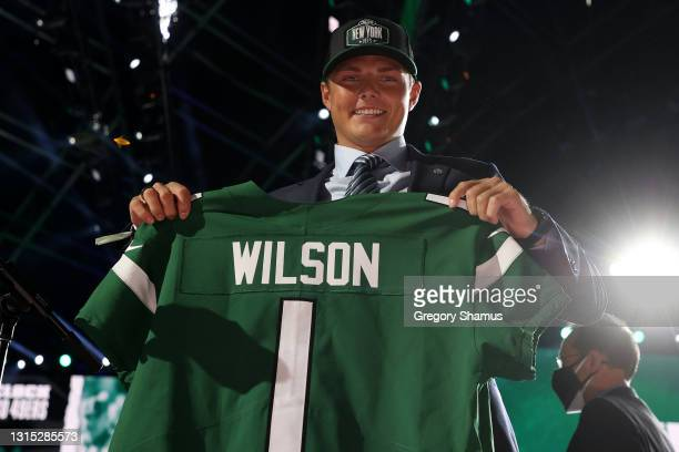 Zach Wilson holds a jersey onstage after being drafted second by the New York Jets during round one of the 2021 NFL Draft at the Great Lakes Science...