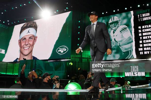 Zach Wilson walks onstage after being drafted second by the New York Jets during round one of the 2021 NFL Draft at the Great Lakes Science Center on...