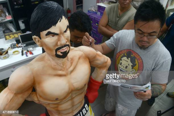 Zach Yonzon creative director and owner of Bunny Baker Cafe decorates a lifesize 70 pound cake worth 4000 USD in the image of Philippine boxer Manny...