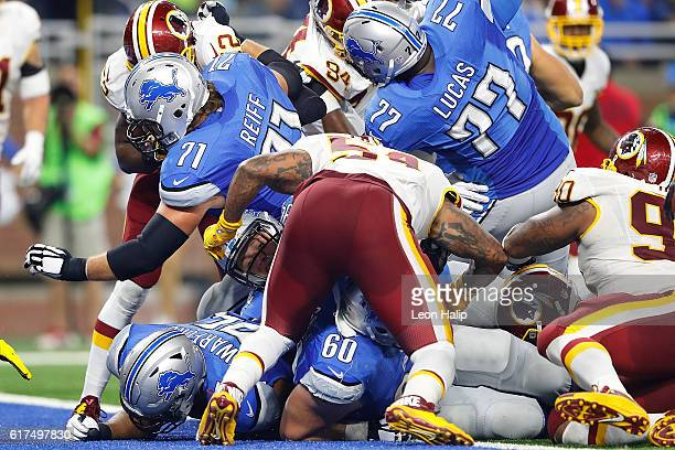 Zach Zenner of the Detroit Lions is buried under his teammates and the Washington Redskins after scoring the first touchdown of the game during third...