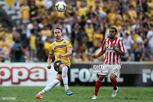 Zachary Anderson of the Mariners kicks the ball ahead of David Williams of Melbourne City during the round 15 ALeague match between the Central Coast...