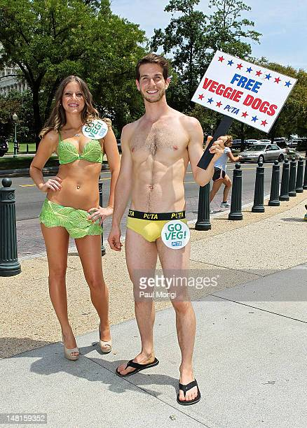 Zachary Koval winner of PETA's Sexiest Vegetarian Contest and a PETA Lettuce Lady pose for a photo during the 'National Veggie Dog Day' event PETA's...