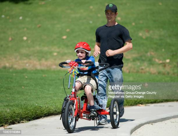 Zachary Stoddard of Laguna Niguel, is chased down by his dad Don after receiving a special tricycle from the non-profit OC's Special Spokes at El...