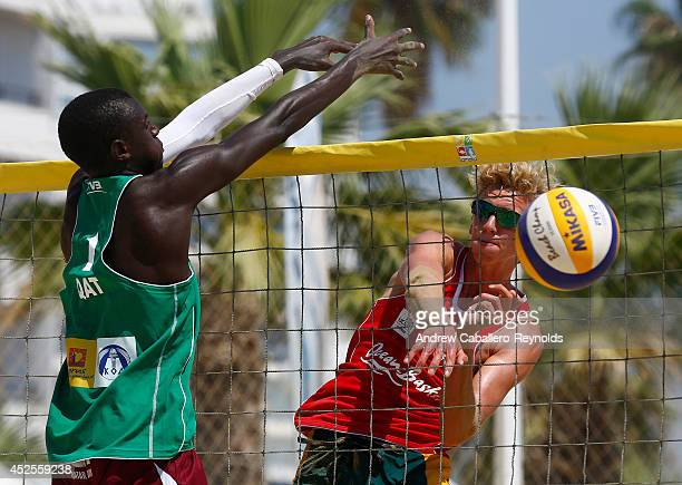 Zachery Schubert from Australia spikes past Cherif Younousse from Qatar at the FIVB Under 21 Beach Vollyball World Championships on July 23 2014 in...