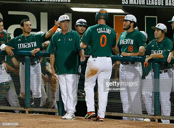 Zack Collins is congratulated by head coach Jim Morris of the Miami Hurricanes after scoring on a wild pitch by the Nova Southeastern Sharks in the...
