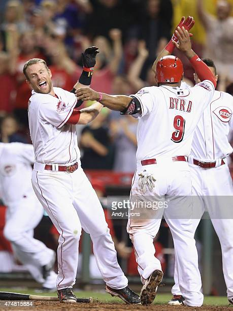 Zack Cozart and Billy Hamilton of the Cincinnati Reds celebrate with Marlon Byrd as he scores the winning run in the 9th inning against the Colorado...