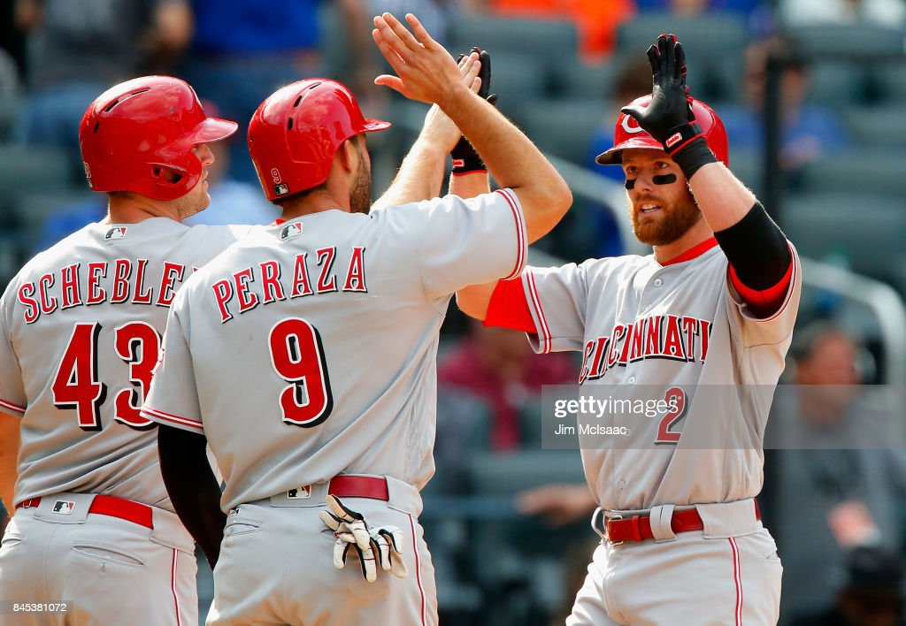 Zack Cozart #2 of the Cincinnati Reds celebrates his seventh-inning, three-run home run against the New York Mets with teammates Scott Schebler #43 and Jose Peraza #9 at Citi Field on September 10, 2017 in the Flushing neighborhood of the Queens borough of New York City.