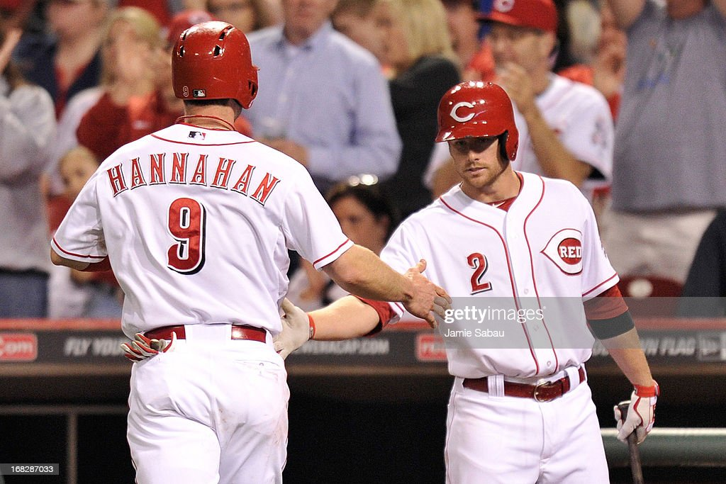 Zack Cozart #2 of the Cincinnati Reds congratulates Jack Hannahan #9 of the Cincinnati Reds after Hannahan scored against the Atlanta Braves in the fifth inning at Great American Ball Park on May 7, 2013 in Cincinnati, Ohio. Cincinnati defeated Atlanta 5-4.