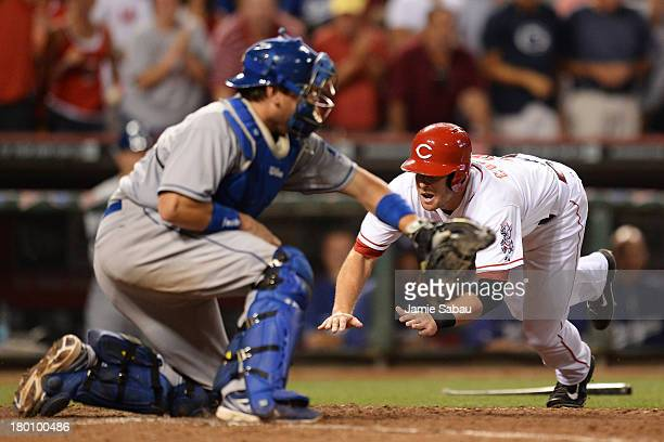 Zack Cozart of the Cincinnati Reds dives in safely at home in the bottom of the ninth inning to score the winning run off a double hit by Ryan...