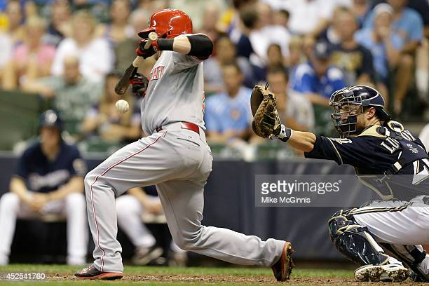 Zack Cozart of the Cincinnati Reds falls after getting hit by a pitch in the top of the seventh inning against the Milwaukee Brewers at Miller Park...
