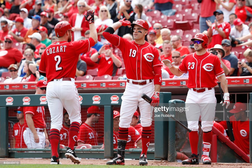 Zack Cozart #2 of the Cincinnati Reds is congratulated by teammates Joey Votto #19 and Adam Duvall #23 after a solo home run in the seventh inning of a game against the Milwaukee Brewers at Great American Ball Park on September 6, 2017 in Cincinnati, Ohio. The Reds defeated the Brewers 7-1.