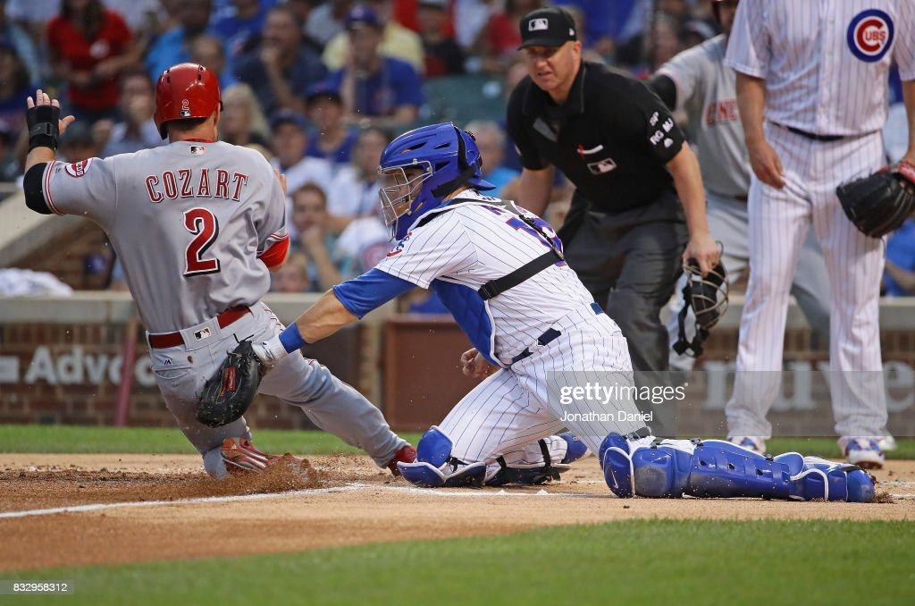 Zack Cozart #2 of the Cincinnati Reds is tagged out at the plate by Alex Avila #13 of the Chicago Cubs in the 1st inning at Wrigley Field on August 16, 2017 in Chicago, Illinois.