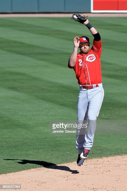 Zack Cozart of the Cincinnati Reds jumps to make the out against the Oakland Athletics during the fourth inning in the spring training game at...