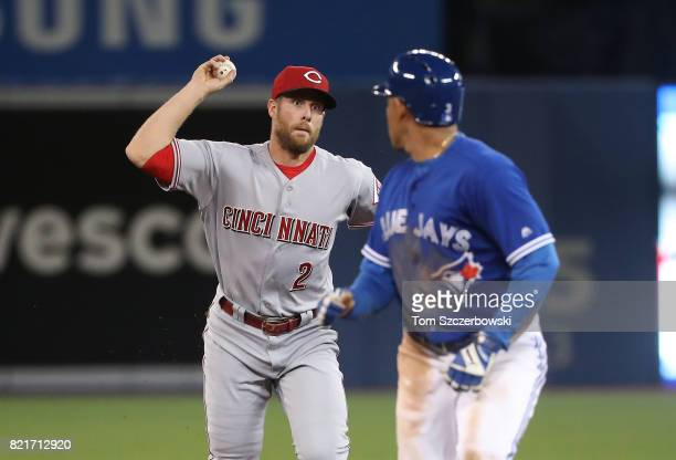 Zack Cozart of the Cincinnati Reds runs down Ezequiel Carrera of the Toronto Blue Jays before tagging him out in the third inning during MLB game...