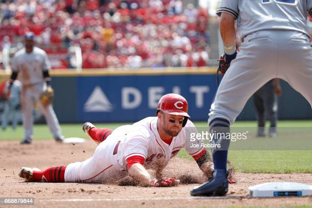 Zack Cozart of the Cincinnati Reds slides safely into third base with an RBI triple in the second inning of a game against the Milwaukee Brewers at...