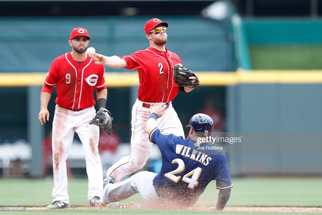 Zack Cozart #2 of the Cincinnati Reds tries to turn a double play over Andy Wilkins #24 of the Milwaukee Brewers in the eighth inning at Great American Ball Park on July 17, 2016 in Cincinnati, Ohio. The Reds defeated the Brewers 1-0.
