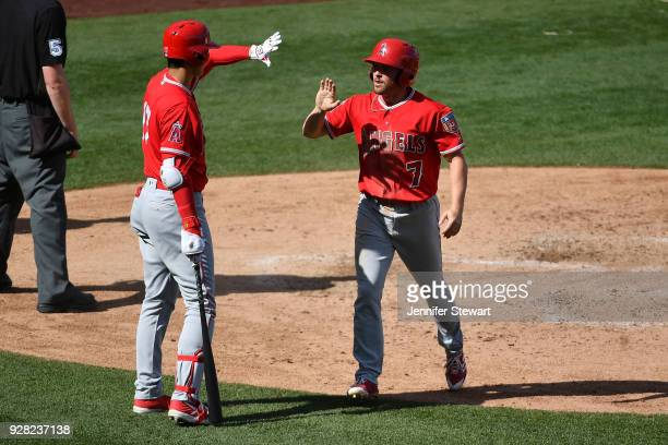 Zack Cozart of the Los Angeles Angels is congratulated by Shohei Ohtani after scoring against the Arizona Diamondbacks in the fifth inning of the...