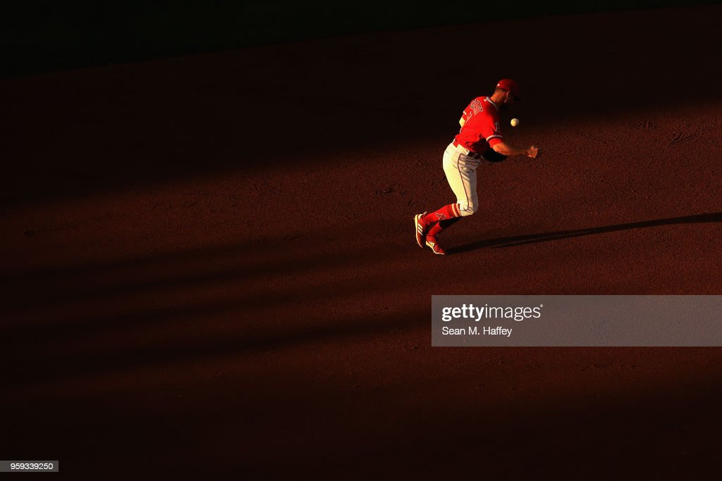Zack Cozart #7 of the Los Angeles Angels of Anaheim bobbles the ball trying to throw out Josh Reddick #22 of the Houston Astros during the first inning of a game at Angel Stadium on May 16, 2018 in Anaheim, California.