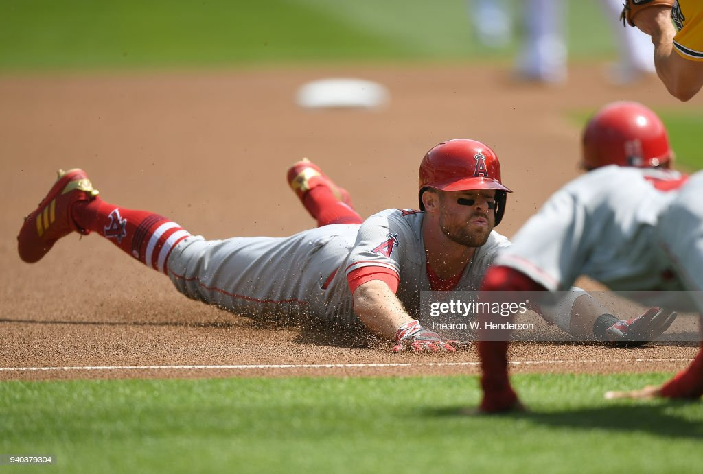 Zack Cozart #7 of the Los Angeles Angels of Anaheim dives into first base with a triple against the Oakland Athletics in the top of the first inning of a Major League Baseball game at Oakland Alameda Coliseum on March 31, 2018 in Oakland, California.