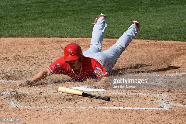 Zack Cozart of the Los Angeles Angels slides into home plate to score against the Arizona Diamondbacks in the fifth inning of the spring training...