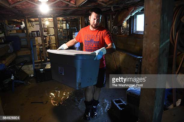 Zack Dickerson red tshirt helps clean out the flooded basement of the home of Michael Kaplan along Frederick Road caused by a flash flood in Ellicott...