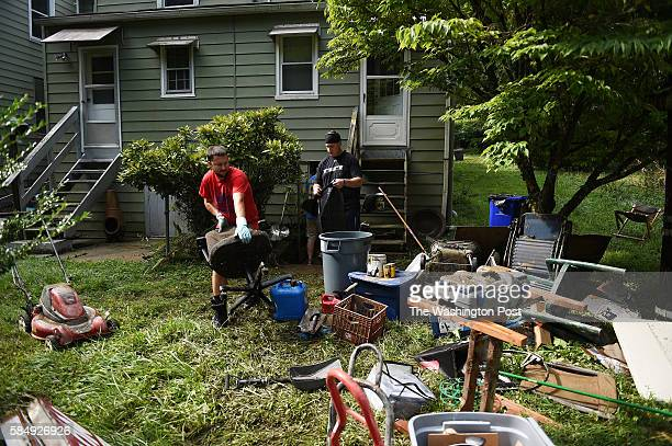 Zack Dickerson red tshirt helps clean out the flooded basement of the home of Michael Kaplan right along Frederick Road caused by a flash flood in...
