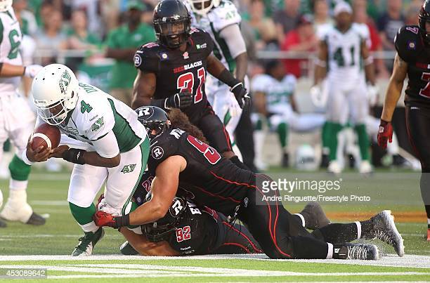 Zack Evans and Connor Williams of the Ottawa Redblacks sack quarterback Darian Durant of the Saskatchewan Roughriders in second quarter action during...