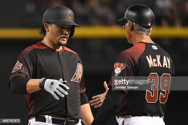 Zack Godley of the Arizona Diamondbacks is congratulated by first base coach Dave McKay after hitting an RBI single during the second inning of the...