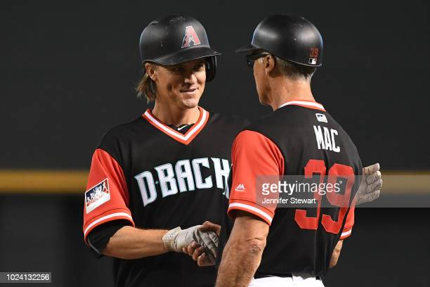 Zack Greinke of the Arizona Diamondbacks is congratulated by first base coach Dave McKay after singling in the third inning of the MLB game against...