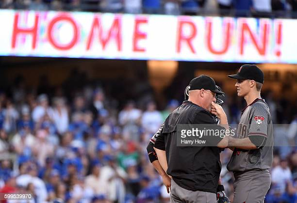 Zack Greinke of the Arizona Diamondbacks receives a visit from pitching coach Mike Butcher after a three run homerun from Corey Seager of the Los...