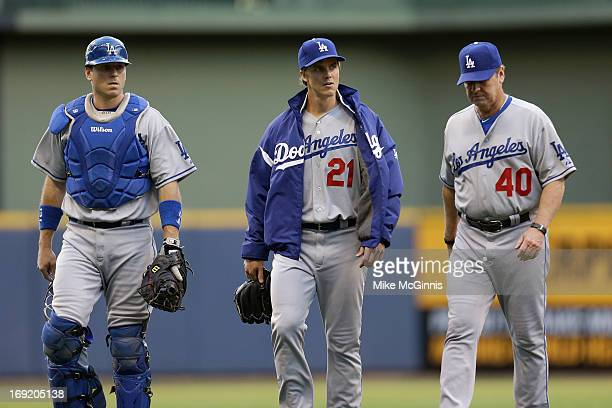 Zack Greinke of the Los Angeles Dodgers walks to the dugout with catcher AJ Ellis and pitching coach Rick Honeycutt before the game against the...
