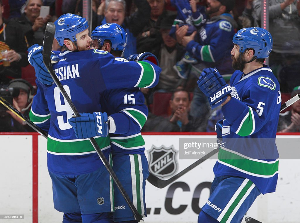 Zack Kassian #9 and Jason Garrison #5 congratulate Brad Richardson #15 of the Vancouver Canucks who scored against the Buffalo Sabres during their NHL game at Rogers Arena March 23, 2014 in Vancouver, British Columbia, Canada.