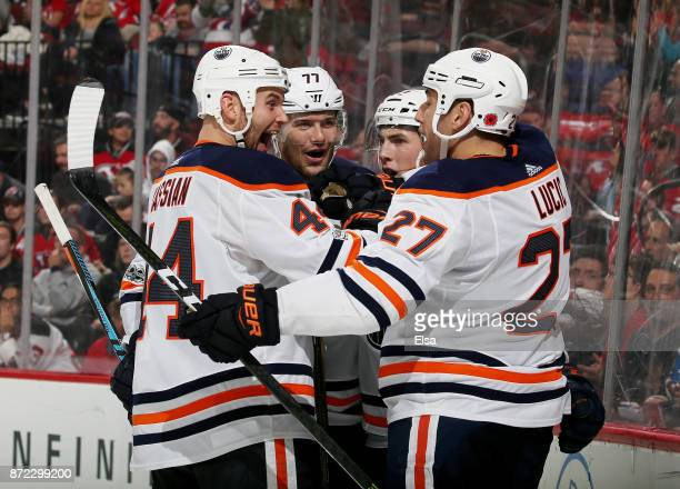 Zack Kassian and Oscar Klefbom of the Edmonton Oilers congratulate teammate Milan Lucic after he scored in the third period against the New Jersey...