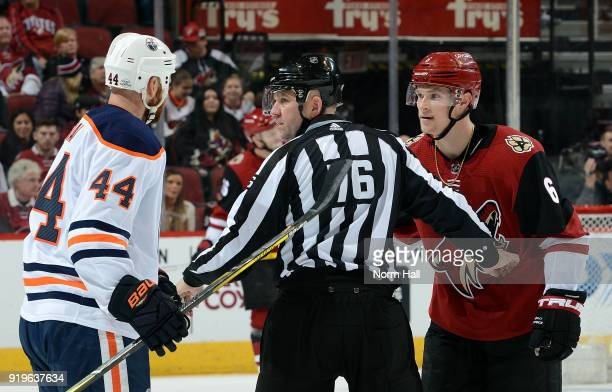 Zack Kassian of the Edmonton Oilers and Jakob Chychrun of the Arizona Coyotes are seperated by linesman Michel Cormier during the first period at...