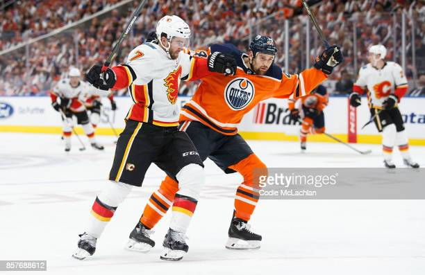 Zack Kassian of the Edmonton Oilers battles against TJ Brodie of the Calgary Flames at Rogers Place on October 4 2017 in Edmonton Canada