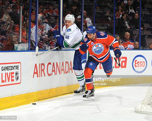 Zack Kassian of the Edmonton Oilers battles for the puck against Nikita Tryamkin of the Vancouver Canucks on March 18 2016 at Rexall Place in...